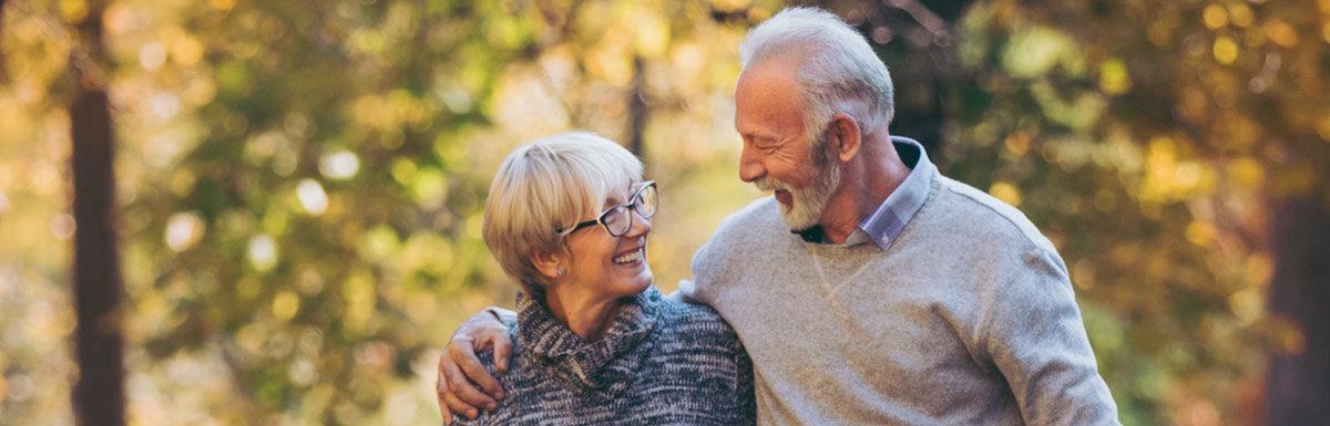 Älteres Paar mit Hund beim Spaziergang in einem herbstlichen Park.