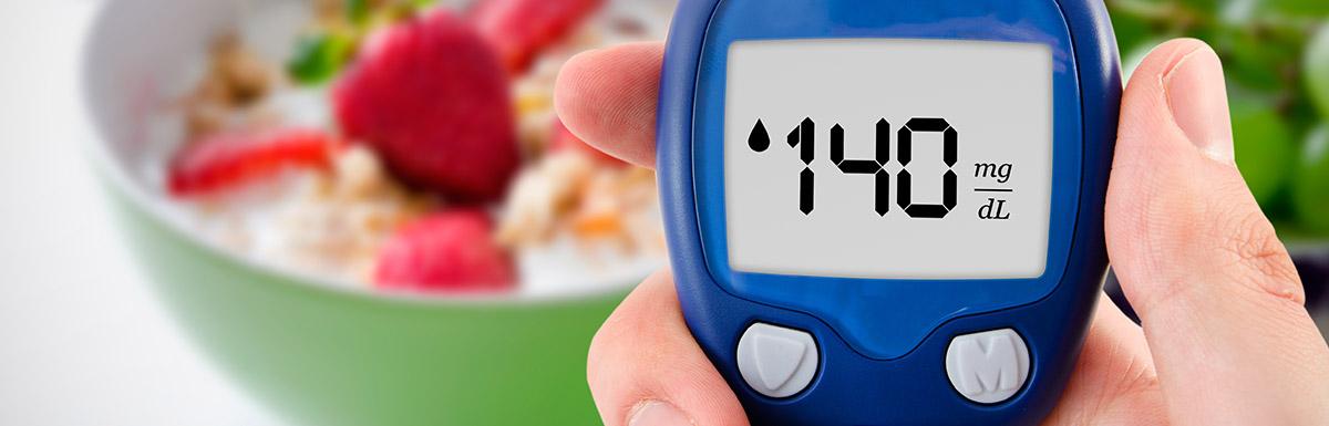 Blutzuckermessgerät zeigt einen Blutzuckerwert von 140 mg/dL an – im Hintergrund eine Schale mit gesundem Essen, das dabei hilft den HbA1c-Wert zu senken.
