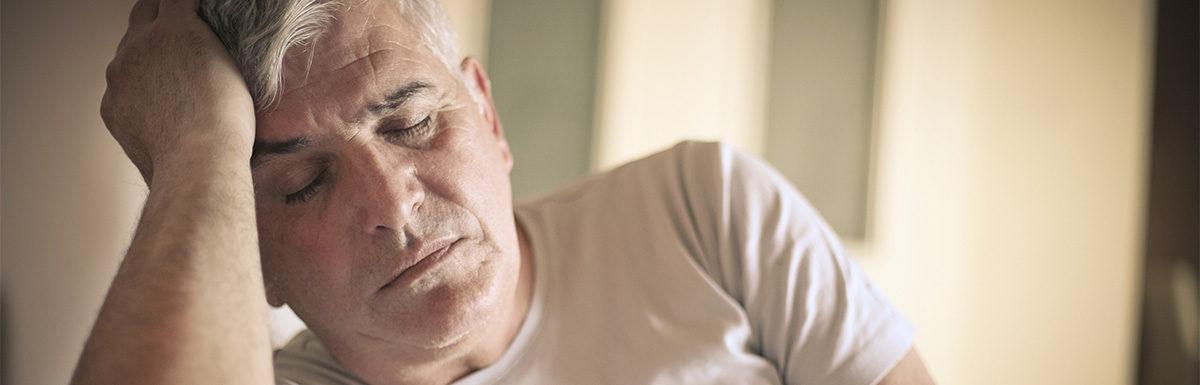 Zu hoher Blutzucker macht müde – erschöpfter Mann sitzt mit geschlossenen Augen auf dem Sofa und stützt seinen Kopf mit der Hand ab.
