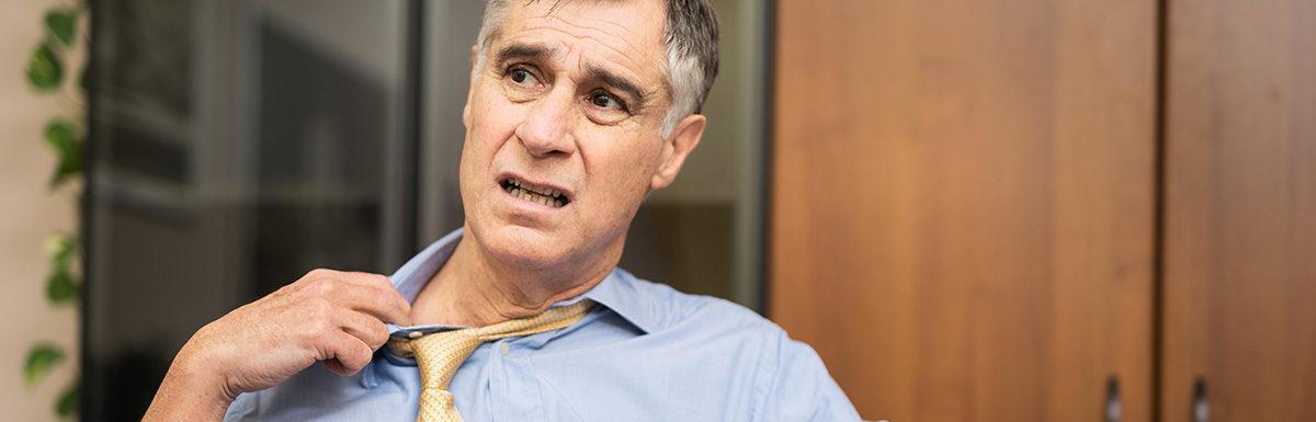 Mann in blauem Hemd und gelber Krawatte zieht gequält an seinem Kragen – Schweiß und Unwohlsein sind mögliche Symptome einer Unterzuckerung.
