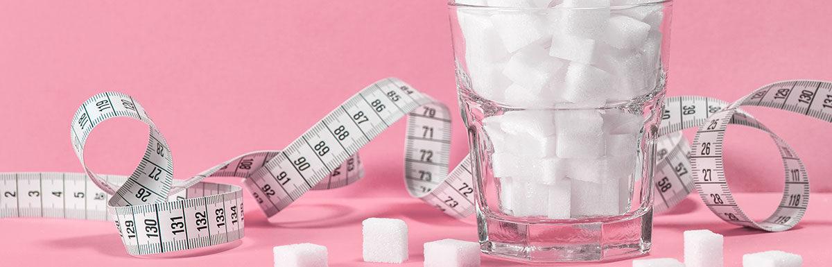 Maßband und Würfelzucker stehen symbolisch für Diabetes Typ 2, der häufig durch falsche Ernährung und Übergewicht ausgelöst wird