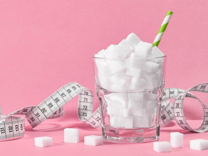 Glas mit Zuckerwürfeln – beim Diabetes Typ 2 sollte die Ernährung zuckerarm sein