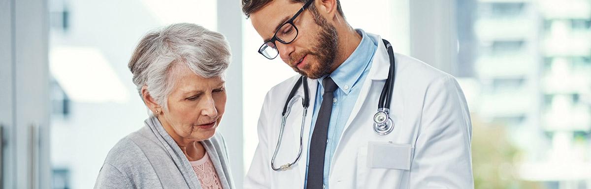 Arzt erklärt älterer Dame ihre Untersuchungsergebnisse im Hinblick auf eine mögliche Diabetes-Diagnose