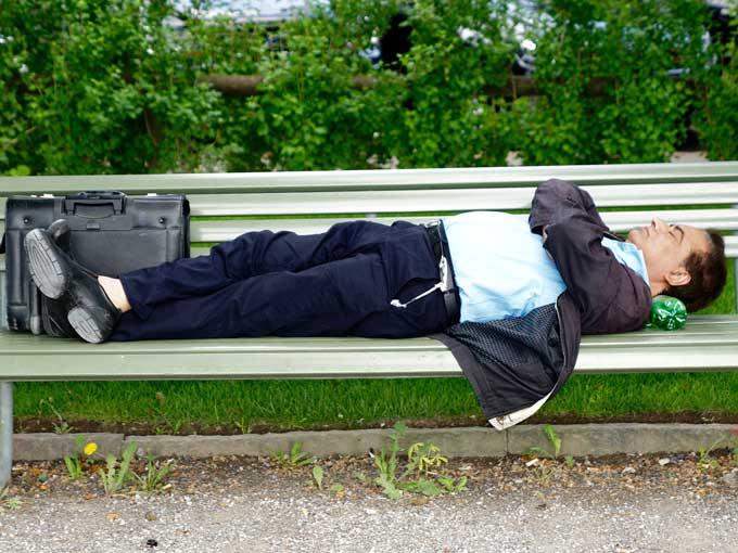 Mann schläft auf Parkbank, da er müde ist. Müdigkeit ist ein Symptom von Diabetes.