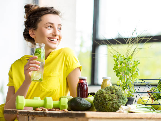 Frau an einem Tisch umgeben von gesunden Nahrungsmitteln, mit denen sie ihren Blutzucker auf natürliche Weise senken kann