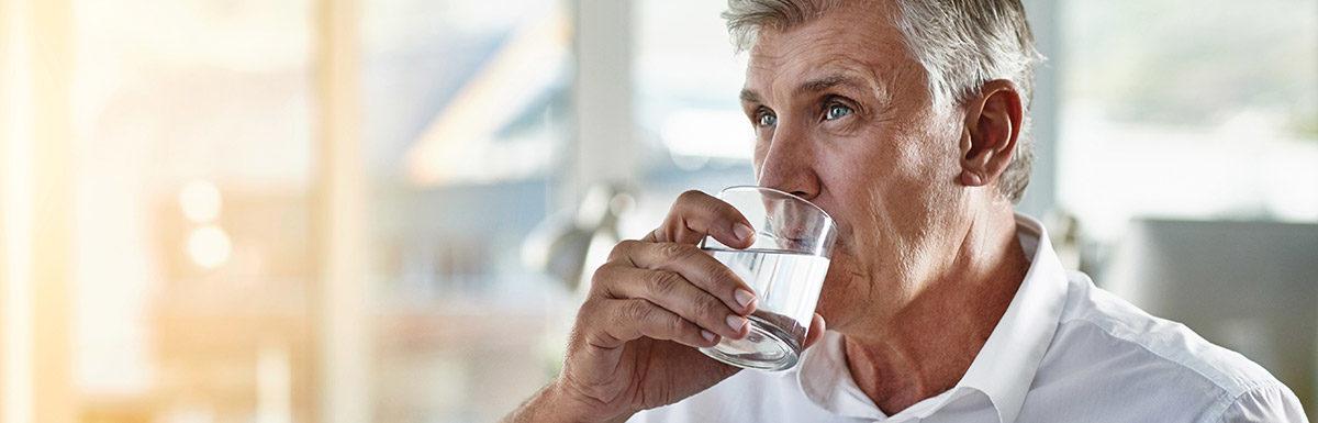 Älterer Mann trinkt aus einem Wasserglas. Vermehrter Durst kann zu den Diabetes-Symptomen gehören.
