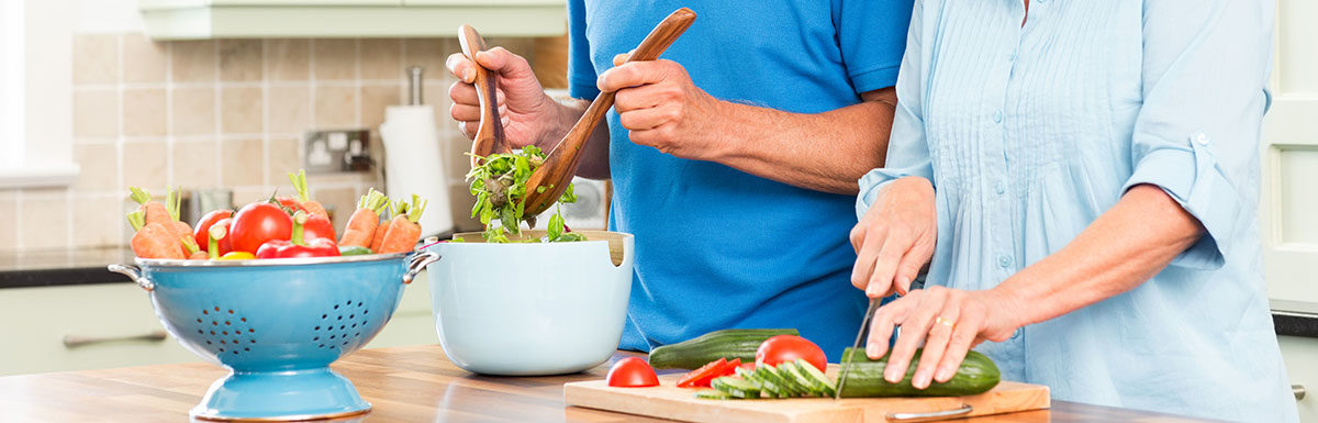 Diabetes und Ernährung: Ein älteres Paar steht in der Küche und bereitet einen Salat zu