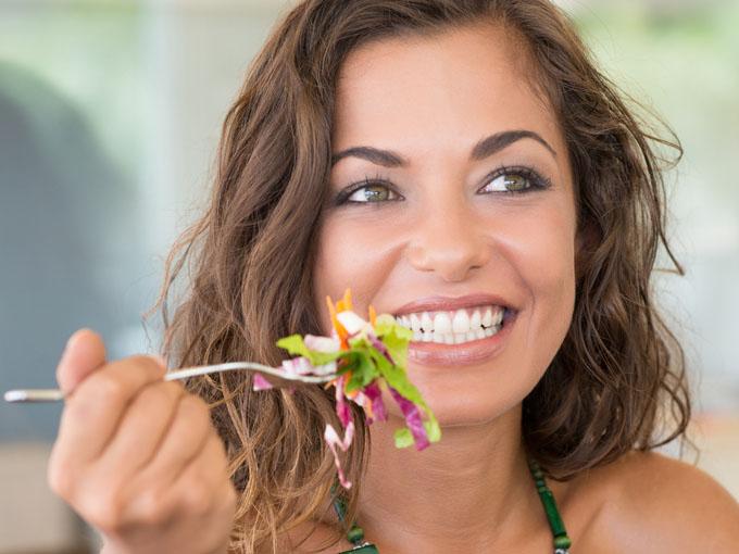 Junge brünette Frau isst einen Salat und meistert ihr Leben mit Diabetes