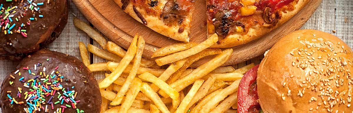 Süßes Gebäck mit Schokoladenüberzug, Pizza, Pommes und Burger. Süßes und fettes Essen kann eine Diabetes-Ursache sein.