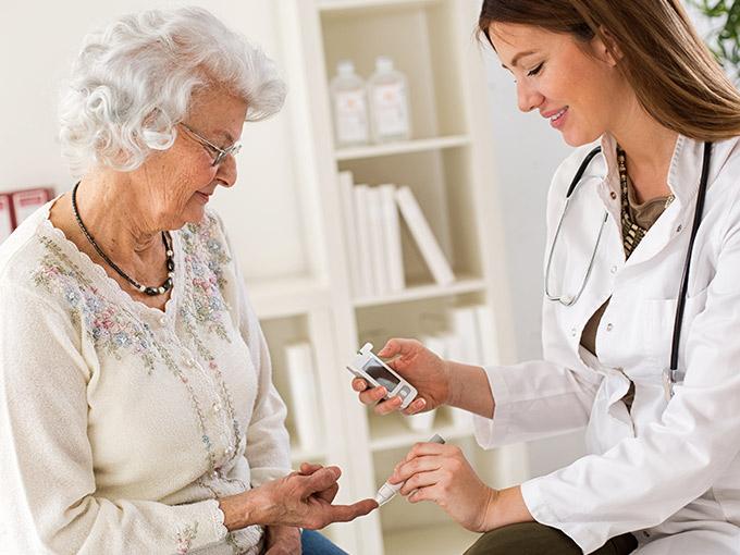 Krankenschwester misst Blutzuckerwerte bei älterer Dame mit Altersdiabetes