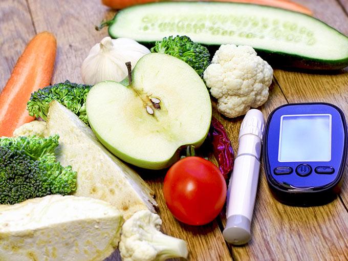Gemüse und Diabetes Messgerät auf einem Holztisch