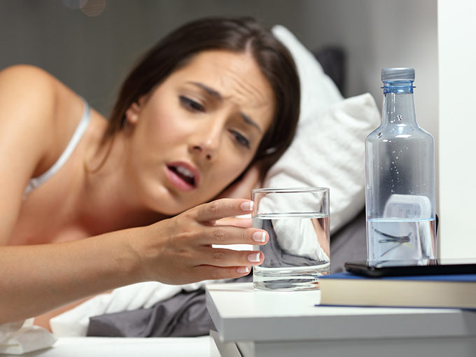 Eine durstige Frau liegt im Bett und schaut auf ein Glas Wasser