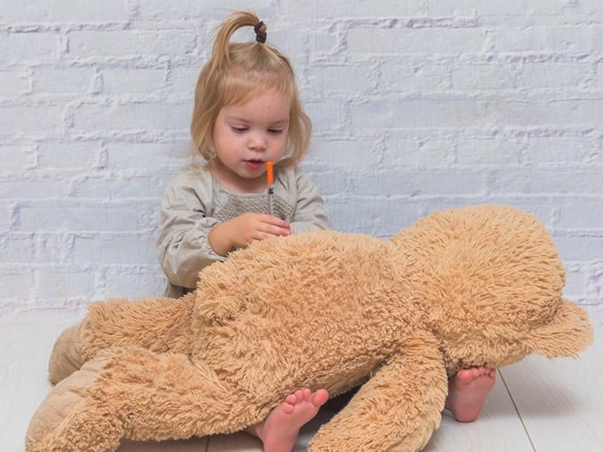 Kleinkind spielt mit einem Teddy und einer Insulinspritze