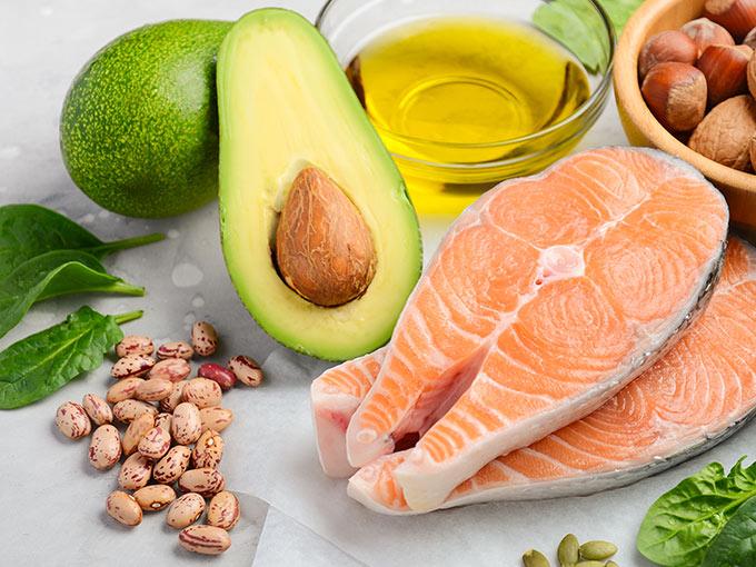 Eine Avocado und ein Stück Fisch als Symbol für gesunde Ernährung