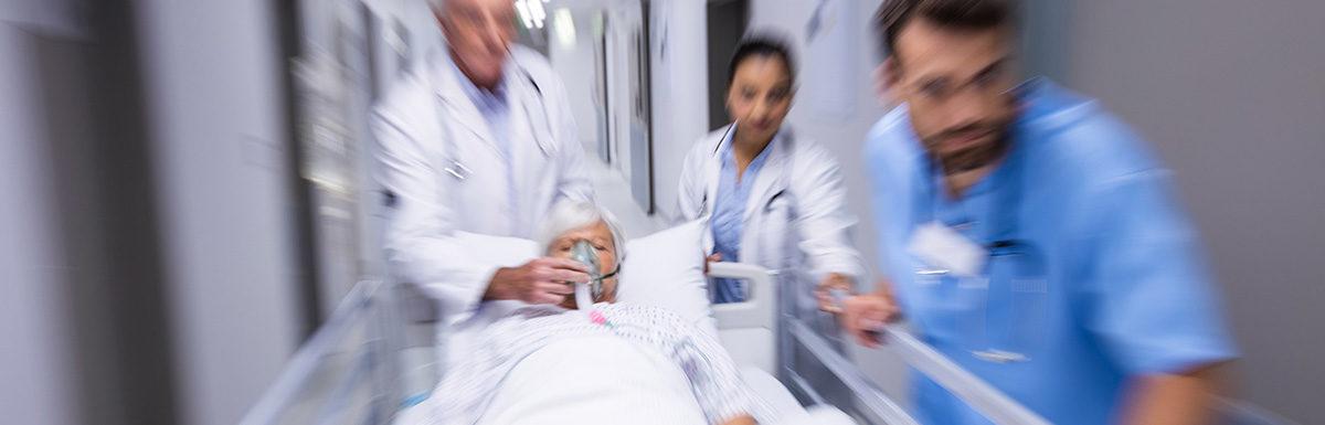 Medizinisches Personal im Krankenhaus schiebt einen Patienten auf einem Bett