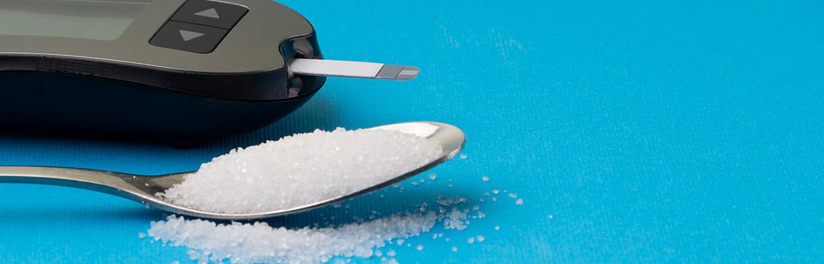 Zucker auf einem Löffel als Symbol für Überzuckerung