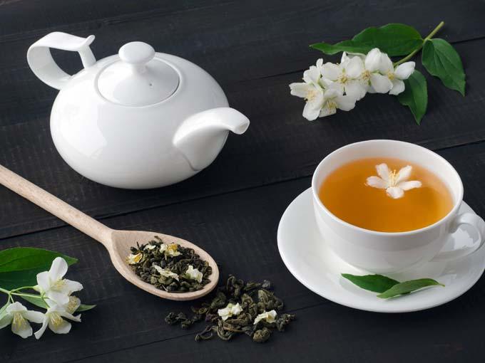Eine Porzellankanne mit grünem Tee und eine Tasse mit Grünem Tee