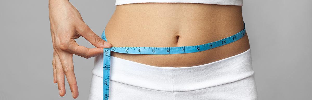 Frau misst ihren Bauchumfang: Abnehmen ist bei Diabetes eine wichtige Therapiemaßnahme.