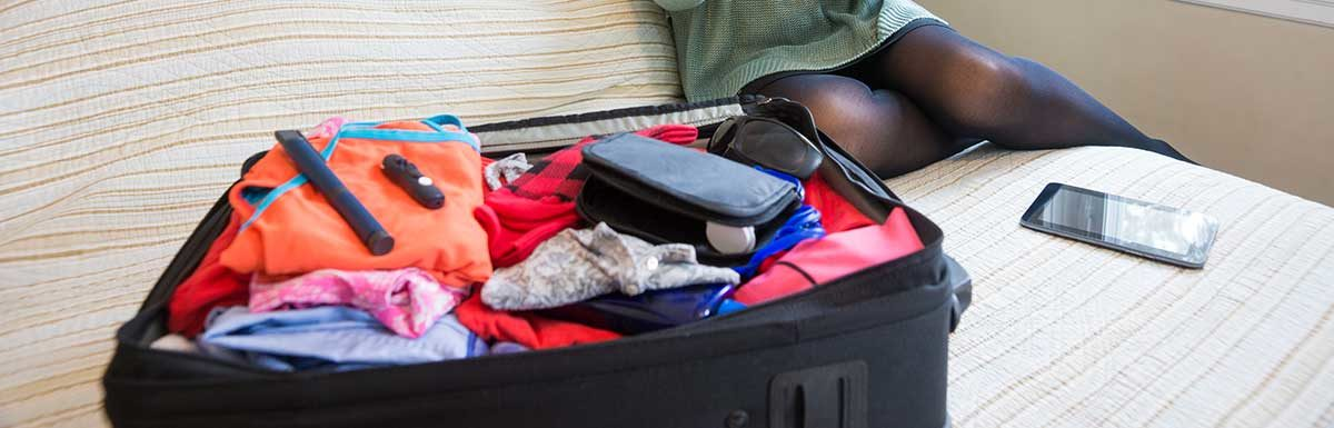 Ein gepackter Koffer auf einem Sofa: Reisen mit Diabetes ist mit einer Insulin-Kühltasche kein Problem.
