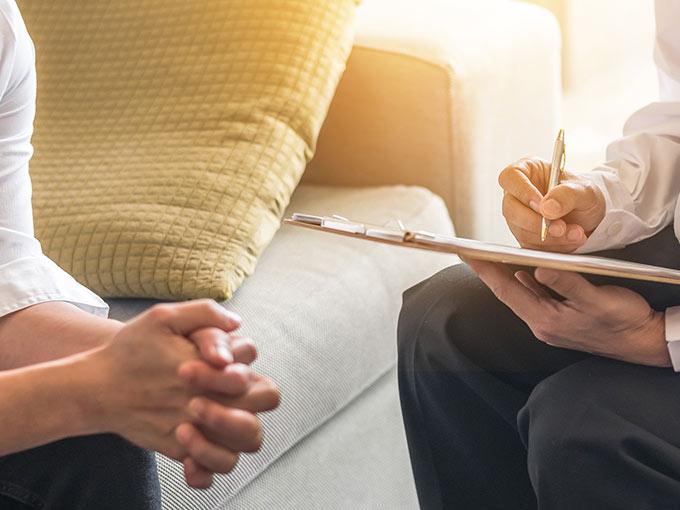 Ein Arzt und ein Patient füllen gemeinsam ein Infoblatt auf einem Klemmbrett aus, um einen Diabetiker-Ausweis zu beantragen.