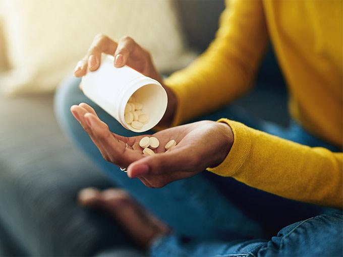 Frau hält einen Behälter mit Tabletten in der Hand - cortisonhaltige Tabletten stehen in Verdacht, Diabetes zu begünstigen.
