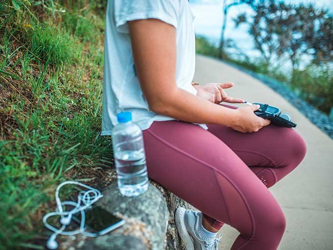 Junge Frau sitzt im Sportoutfit und mit Wasserflasche im Freien - Bewegung bei Diabetes hilft, die Krankheit in den Griff zu bekommen.