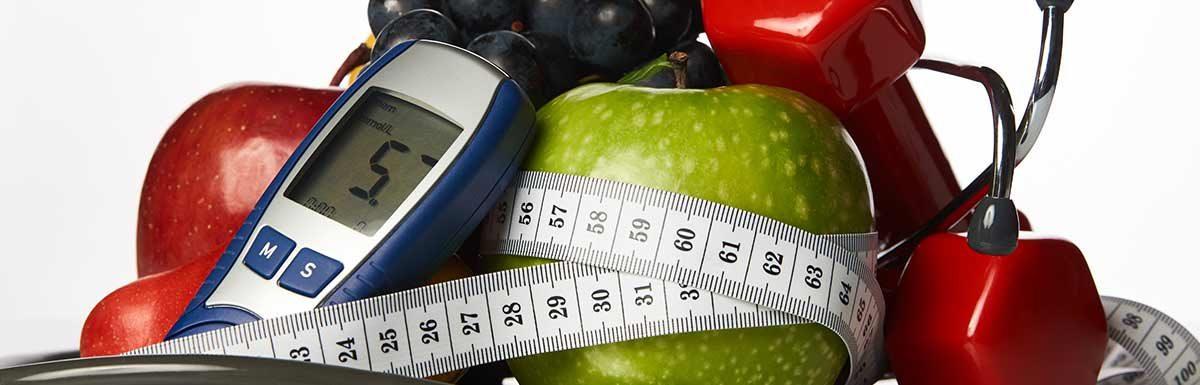 Maßband, Äpfel und ein Blutzuckermessgerät vor weißem Hintergrund: Bei Diabetes Sport zu treiben ist sehr empfehlenswert.