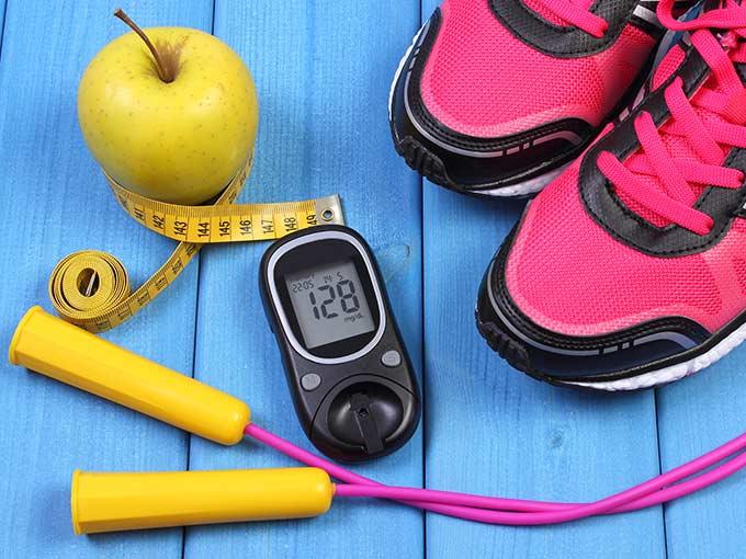 Maßband, Turnschuhe, Springseil und Blutzuckermessgerät vor blauem Hintergrund: Sport bei Diabetes kann helfen, den Blutzucker zu stabilisieren.
