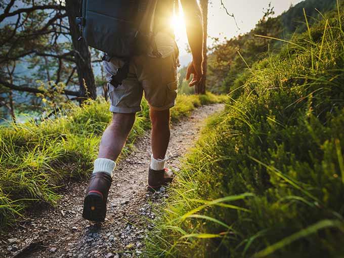 Wanderer mit Rucksack unterwegs in der Natur - ausreichend Bewegung kann einer diabetischen Angiopathie vorbeugen.