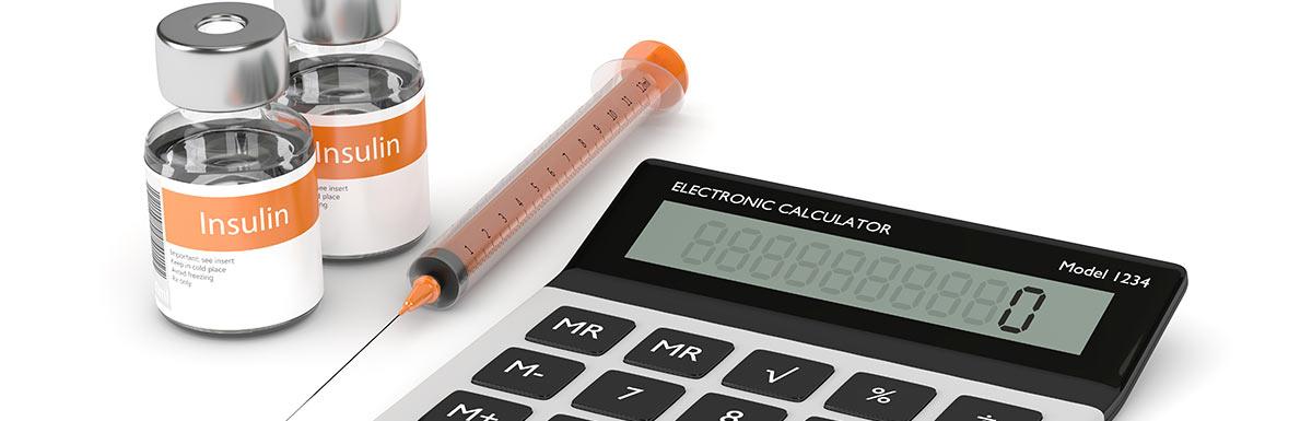 Ein Taschenrechner liegt neben einer Spritze und Insulin-Ampullen. Den HbA1c zu berechnen ist für Diabetespatienten wichtig.
