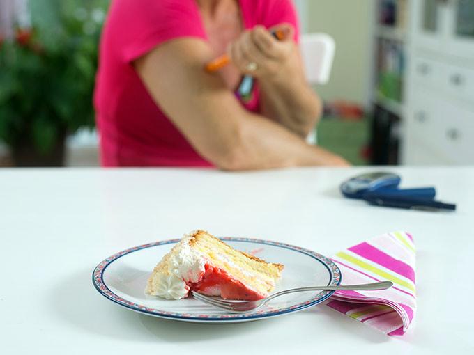 Im Vordergrund steht ein Stück Kuchen auf einem Tisch, im Hintergrund spritzt sich eine Diabetikerin Insulin - mit Diabetes ist es wichtig, keinen Korrekturfaktor zu kennen.