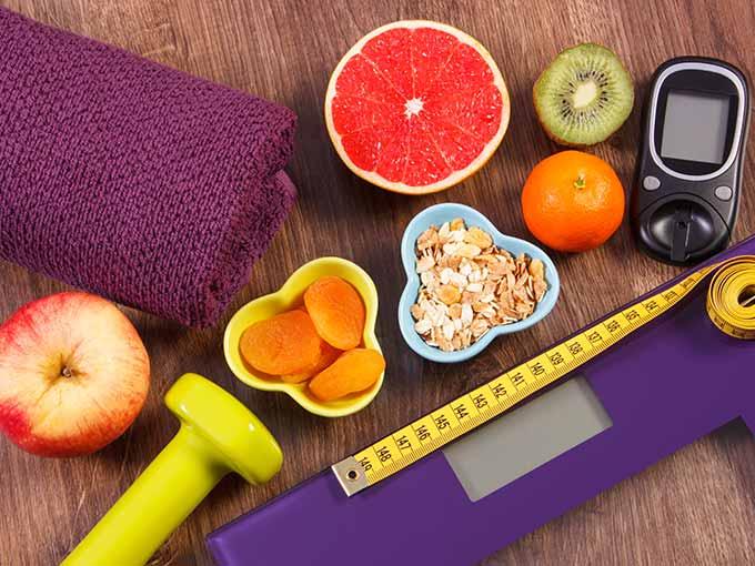 Eine Waage, verschiedenes Obst und ein Maßband liegen auf einem Tisch: Wer im Umgang mit seiner Erkrankung selbstsicher werden möchte, sollte seinen Korrekturfaktor bei Diabetes berechnen.