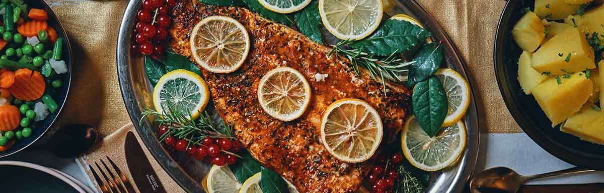 Fisch mit Zitronenscheiben garniert und neben Gemüsebeilagen auf einem Tablett - Fisch zählt zu den blutdrucksenkenden Lebensmitteln.