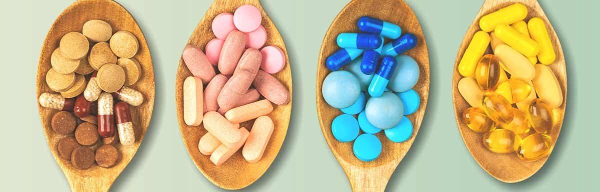 Verschiedenfarbige Pillen auf Holzlöffeln - Nahrungsergänzungsmittel können bei Diabetes sinnvoll sein.