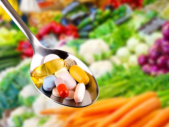 Bunte Tabletten auf einem Löffel - für Diabetiker kann Nahrungsergänzung sinnvoll sein.