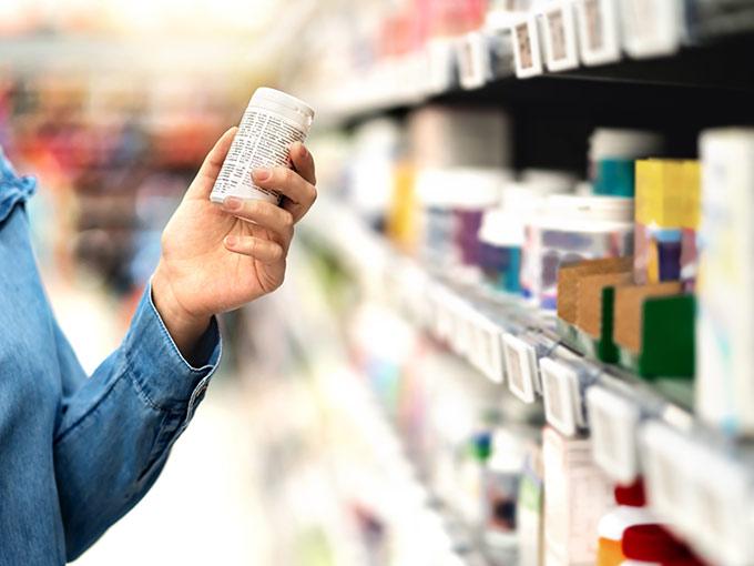 Mann steht vor einem Supermarktregal und inspiziert eine Tablettenverpackung: Bei Diabetes werden Nahrungsergänzungsmittel oft zur begleitenden Therapie eingesetzt.