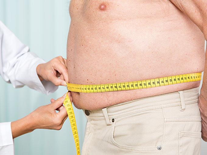 Arzt misst den Bauchumfang eines Patienten - viel Bauchfett kann eine pathologische Glukosetoleranz begünstigen.