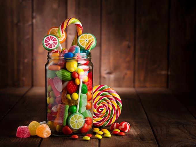 Ein Glas mit bunten Süßigkeiten - viel Fett und Zucker in der Nahrung können eine pathologische Glukosetoleranz auslösen.