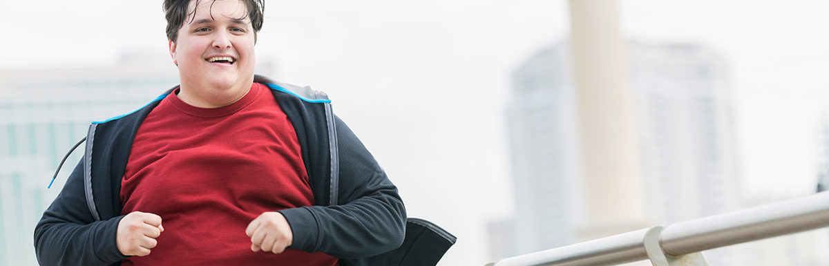 Ein übergewichtiger Mann in Sportklamotten beim Joggen - den Blutdruck senken kann durch Sport gelingen.
