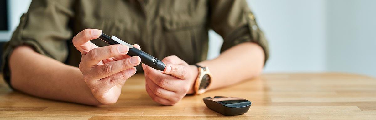 Eine junge Frau sticht sich in die Fingerkuppe, um ihren Blutzucker zu messen: Ein niedriger Blutzucker gehört zu den Symptomen bei Diabetes mellitus Typ 3.