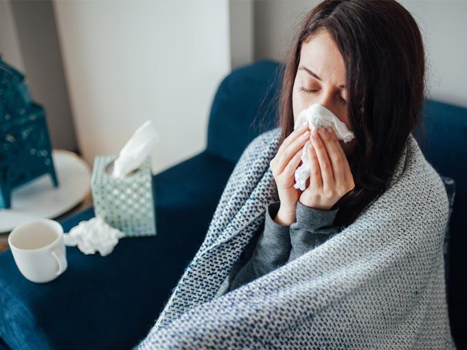 Eine junge Frau putzt sich in eine Decke eingewickelt die Nase - häufige Erkältungen gehören zu den Diabetes-Typ-3-Symptomen.