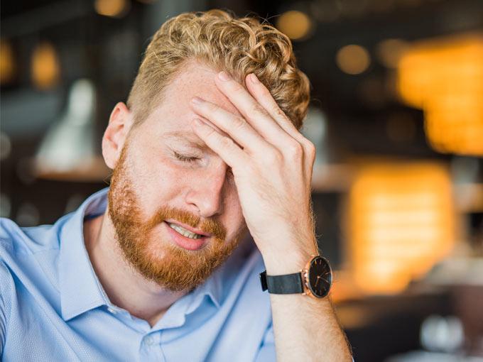 Ein junger rothaariger Mann fasst sich mit schmerzverzerrtem Gesicht an die Stirn: Kopfschmerzen können auf Diabetes mellitus Typ 3 hinweisen.