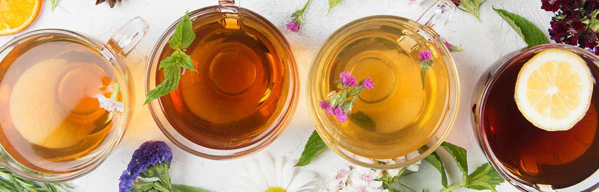 Verschiedene gefüllte Teegläser von oben fotografiert auf einem Tisch: Bestimmte Sorten Tee können den Blutdruck senken.