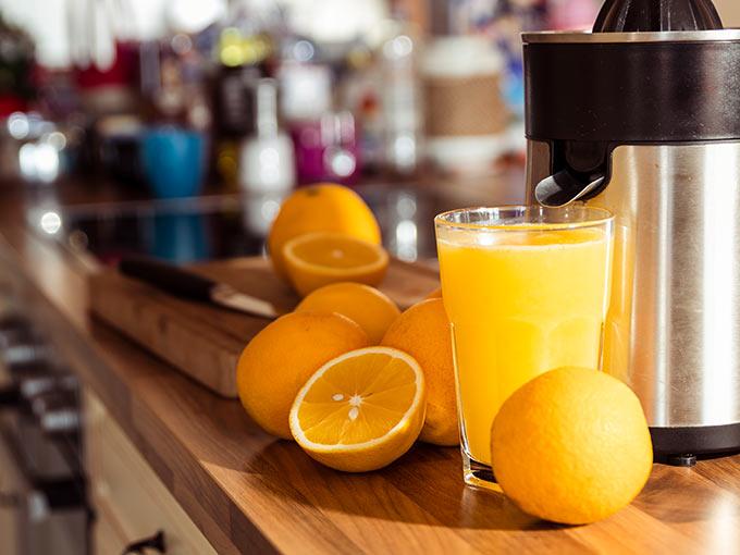 Mehrere Orangen liegen neben einem Glas frisch gepresstem Saft - bei der Therapie einer Unterzuckerung kann Fruchtzucker hilfreich sein.