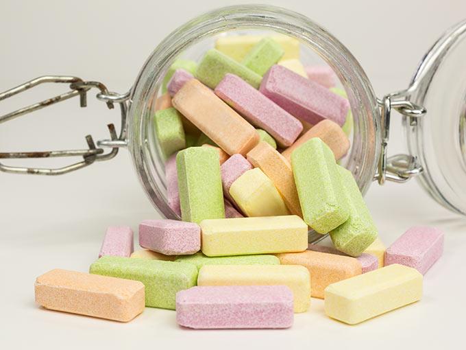 Bunter Traubenzucker in einem Glas: Für die rechtzeitige Behandlung einer Unterzuckerung sollten Diabetes-Patienten stets Traubenzucker mit sich führen.