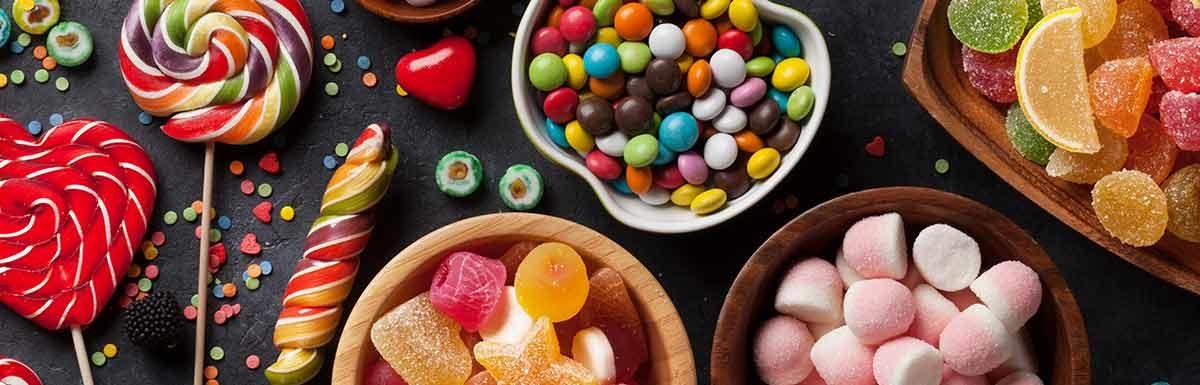 Ein Tisch voller bunter Süßigkeiten - für die Behandlung einer Unterzuckerung dürfen Diabetiker*innen auch zu zuckerhaltigen Speisen greifen.