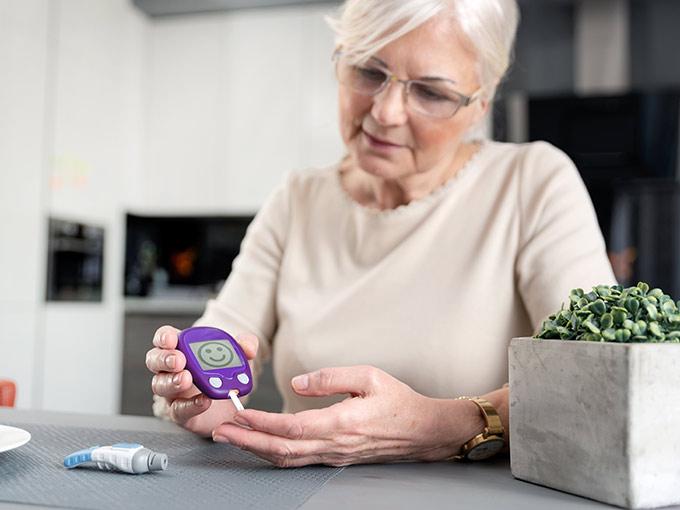 Ältere Frau misst ihren Blutzucker: Glycowohl-Studien belegen die Wirksamkeit des Arzneimittels bei Diabetes.