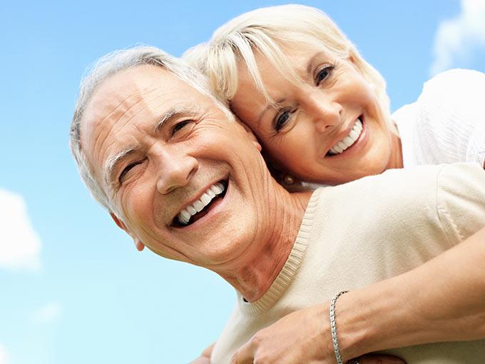 Älteres Paar lacht in die Kamera.