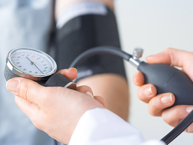 Ein Arzt hält ein Blutdruckmessgerät in der Hand - Diabetiker sollten ihren Blutdruck senken.