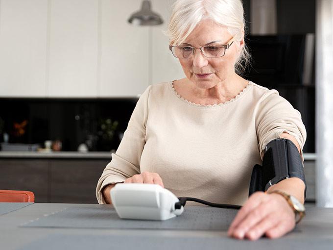 Eine ältere Frau mit Brille misst ihren Blutdruck mithilfe eines Messgeräts.